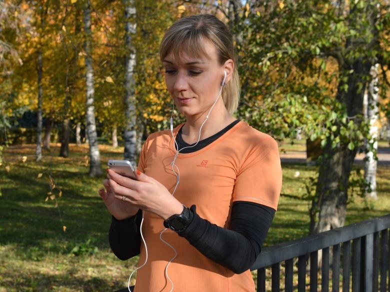 Kuva, jossa juoksija musiikkia puhelimestaan.