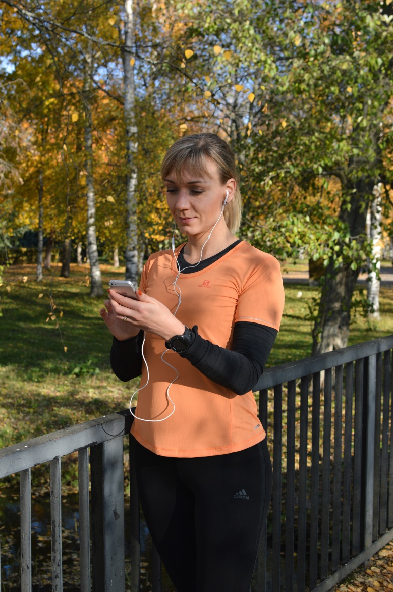Kuva, jossa nainen kuuntelee musiikkia puhelimesta.