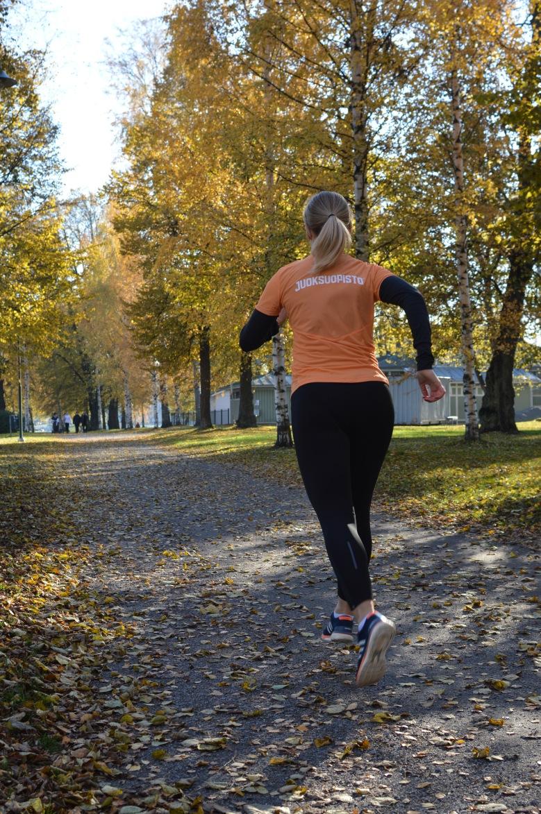 Kuva, jossa nainen juoksee poisapain kamerasta.