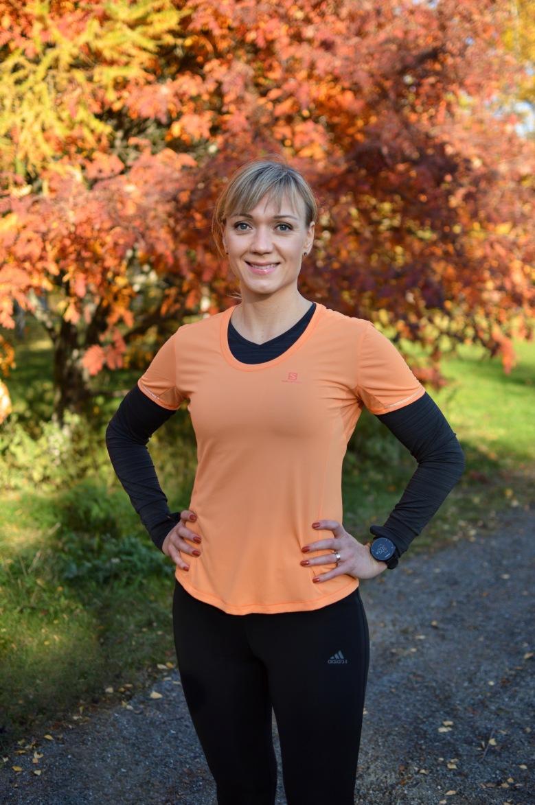 Kuva, jossa nainen seisoo oranssin pihlajan edessa.