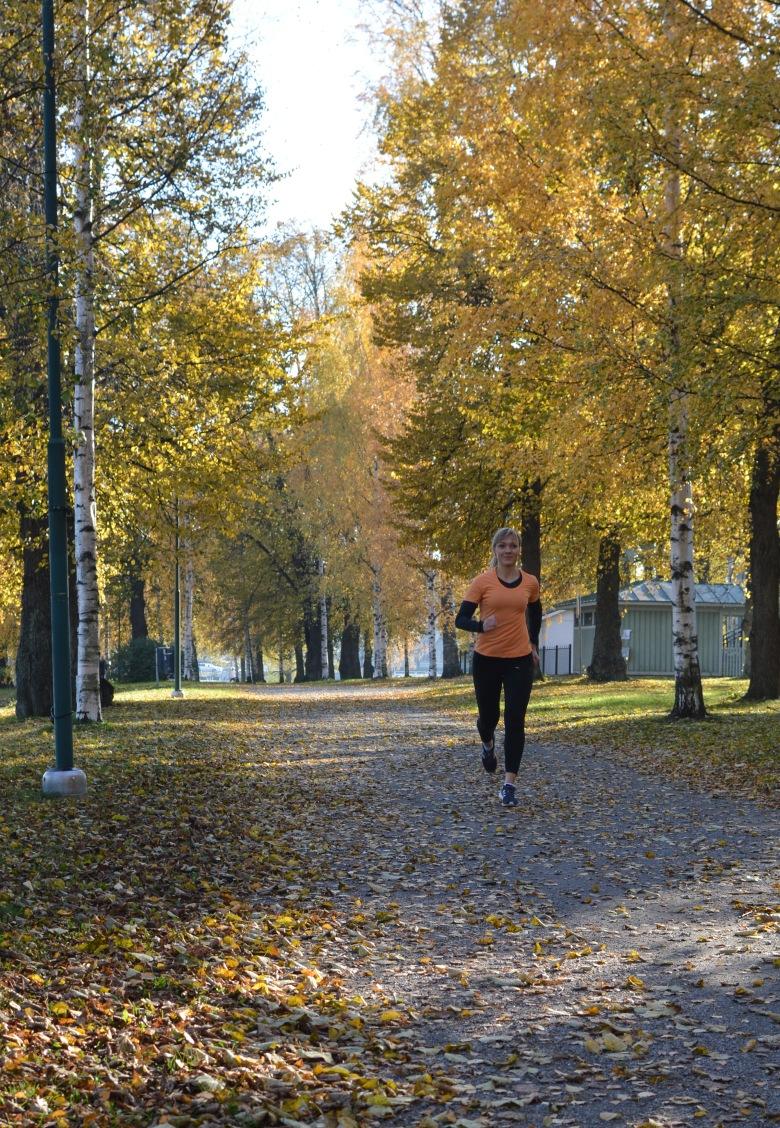 Kuva, jossa juoksija juoksee puiden lehtien seassa.