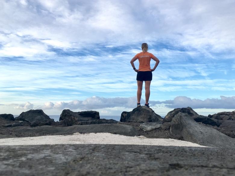 Kuva, jossa nainen seisoo kivella ja katsoo horisonttiin.
