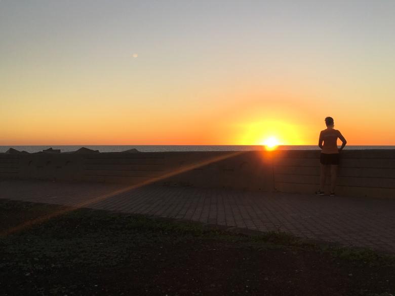Kuva, jossa juoksija katsoo laskevaa aurinkoa.