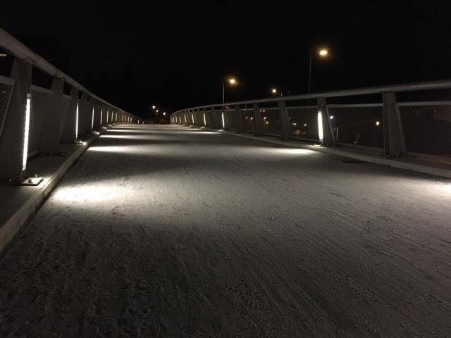 Kuva, jossa lunta ja valaistu silta.