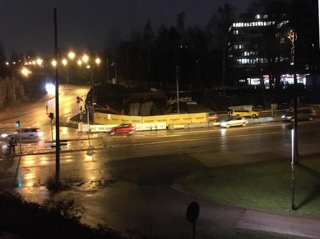 Kuva, jossa on mustaa asfalttia ja autoja.