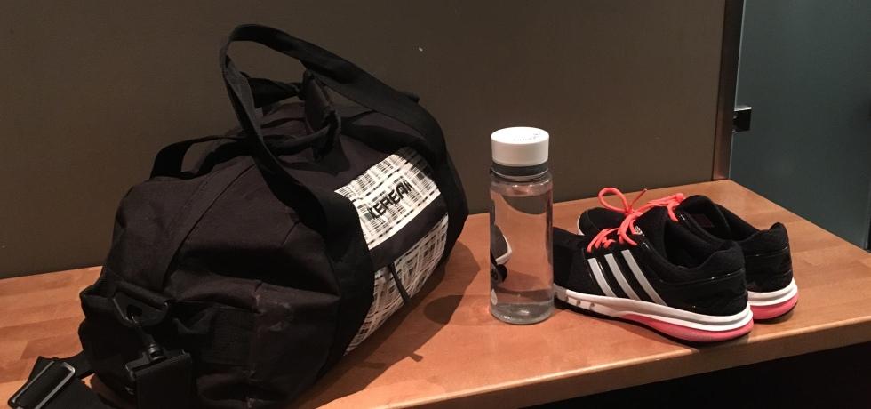 Kuva, jossa treenikassa, juomapullo ja lenkkarit.