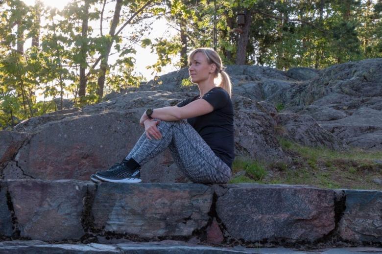 Kuva, jossa nainen istuu kalliolla.