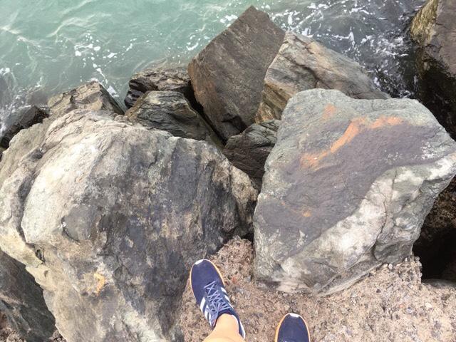 kuva, jossa lenkkitossut kiven reunalla.