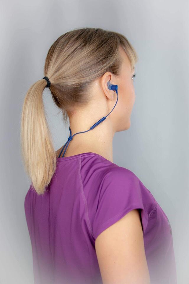 Kuva, jossa bluetooth kuulokkeiden johto niskassa.