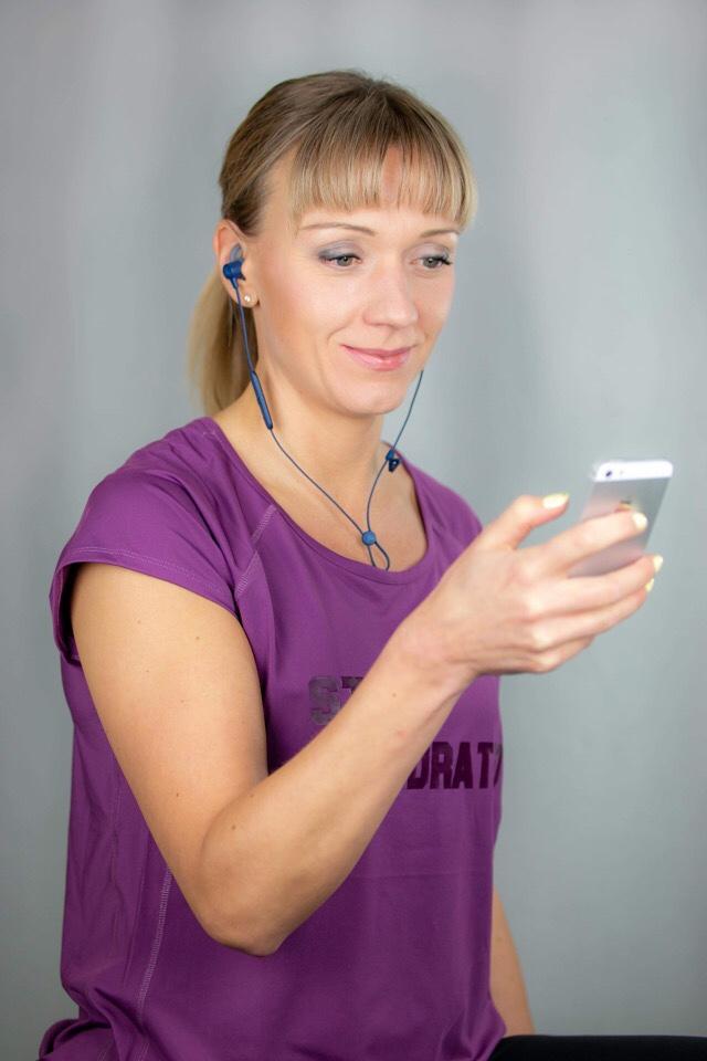 Kuva, jossa nainen katsoo puhelinta kuulokkeet korvilla.