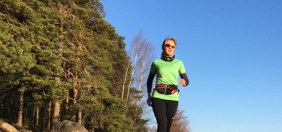 Kuva, jossa nainen juoksija juoksee rannalla.