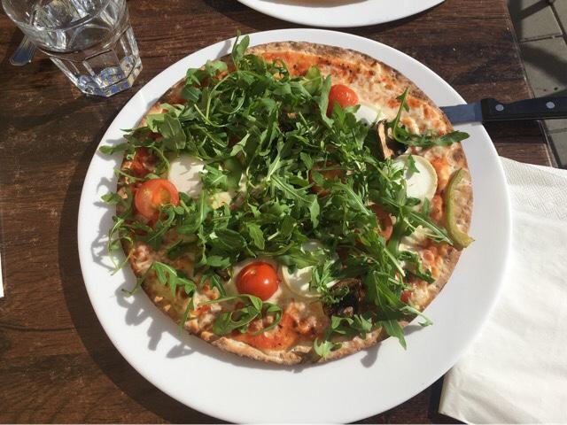 Kuva, jossa pizzan päällä rucolaa.