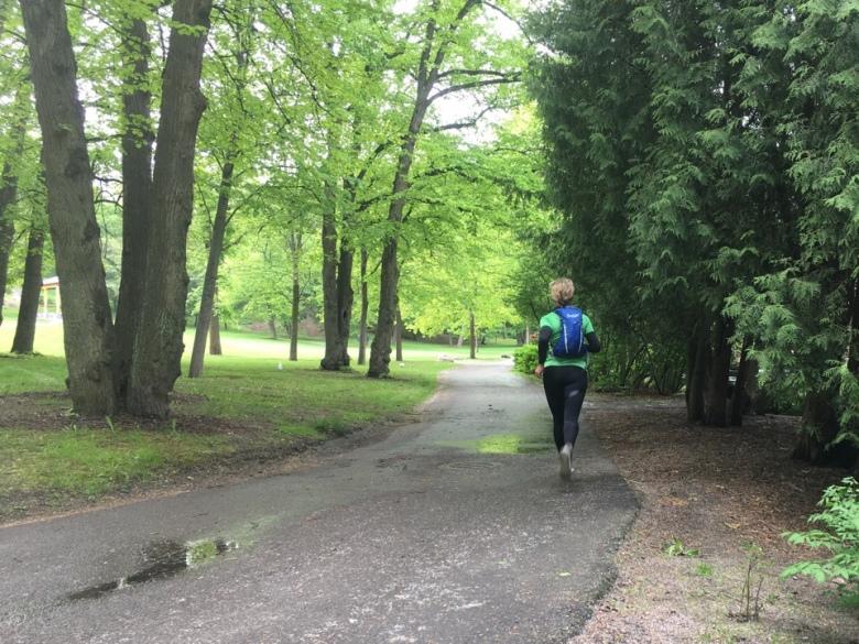Kuva, jossa juoksija puistossa.