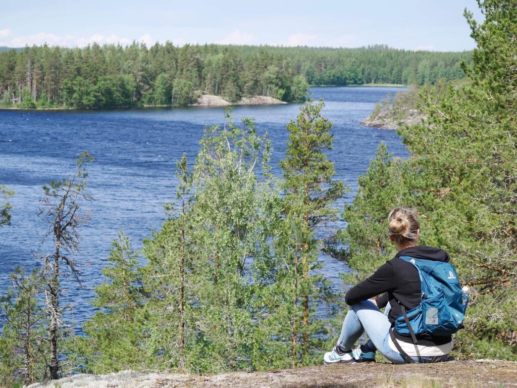 Kuva, jossa retkeilija istuu kalliolla.