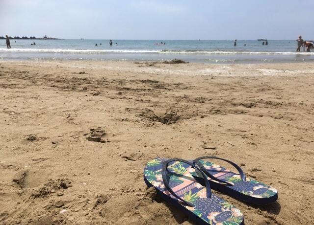 Kuva, jossa varvassandaalit rannalla
