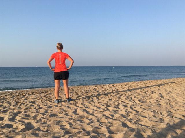 Kuva, jossa juoksija meren rannalla.