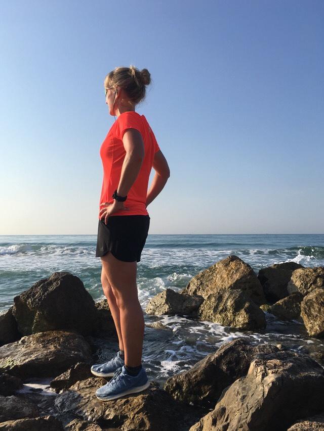 Kuva, jossa juoksija seisoo rannalla.