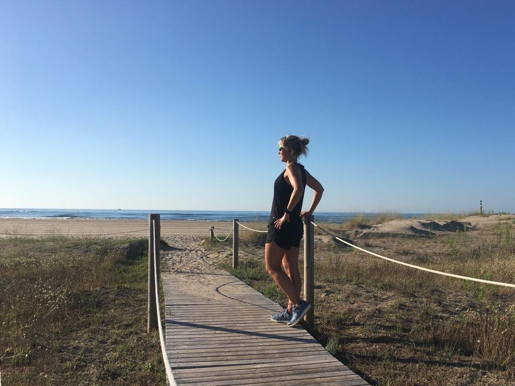 Kuva, jossa juoksija hiekkarannalla