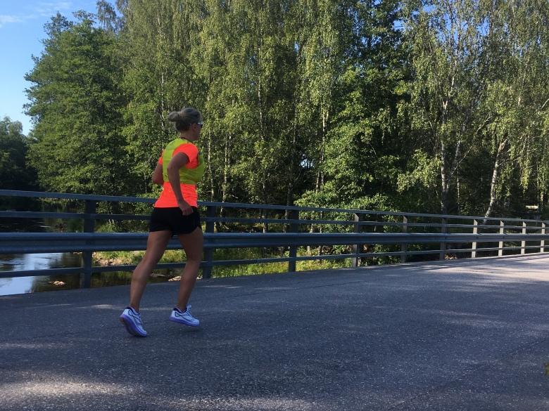 Kuva, jossa juoksija sillalla.