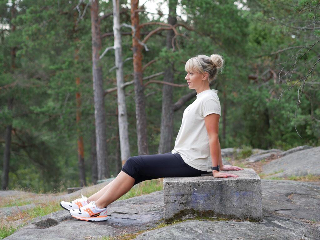Kuva, jossa juoksija istuu betonin päällä.