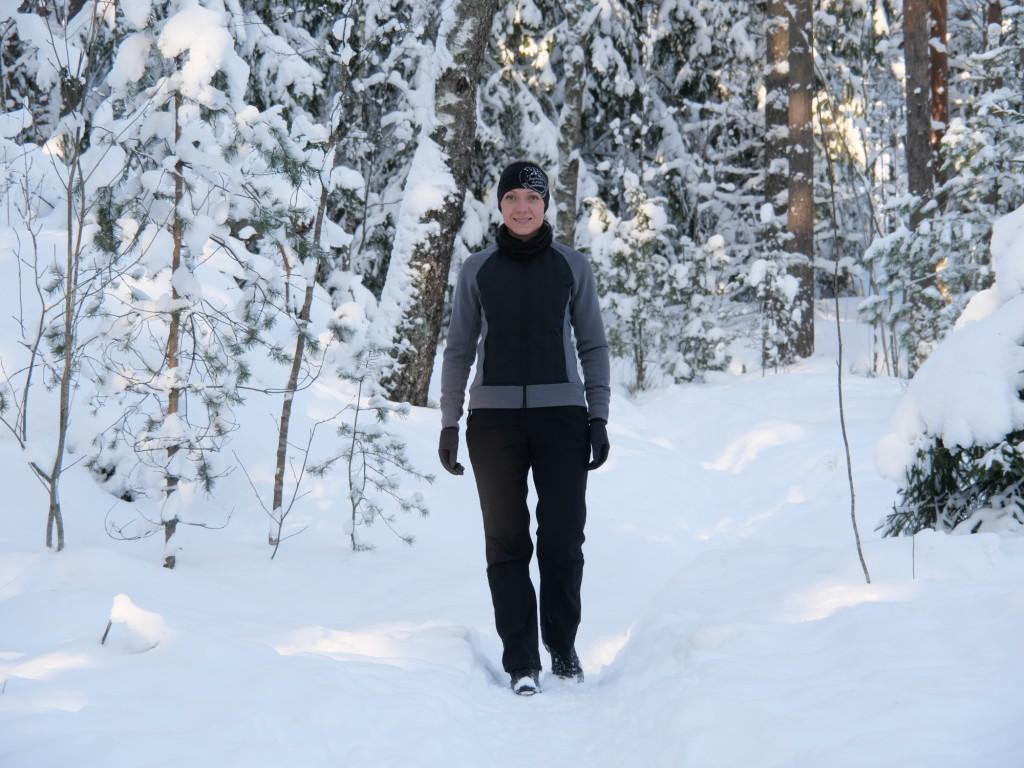 kuva, jossa nainen kavelee lumisessa metsassa